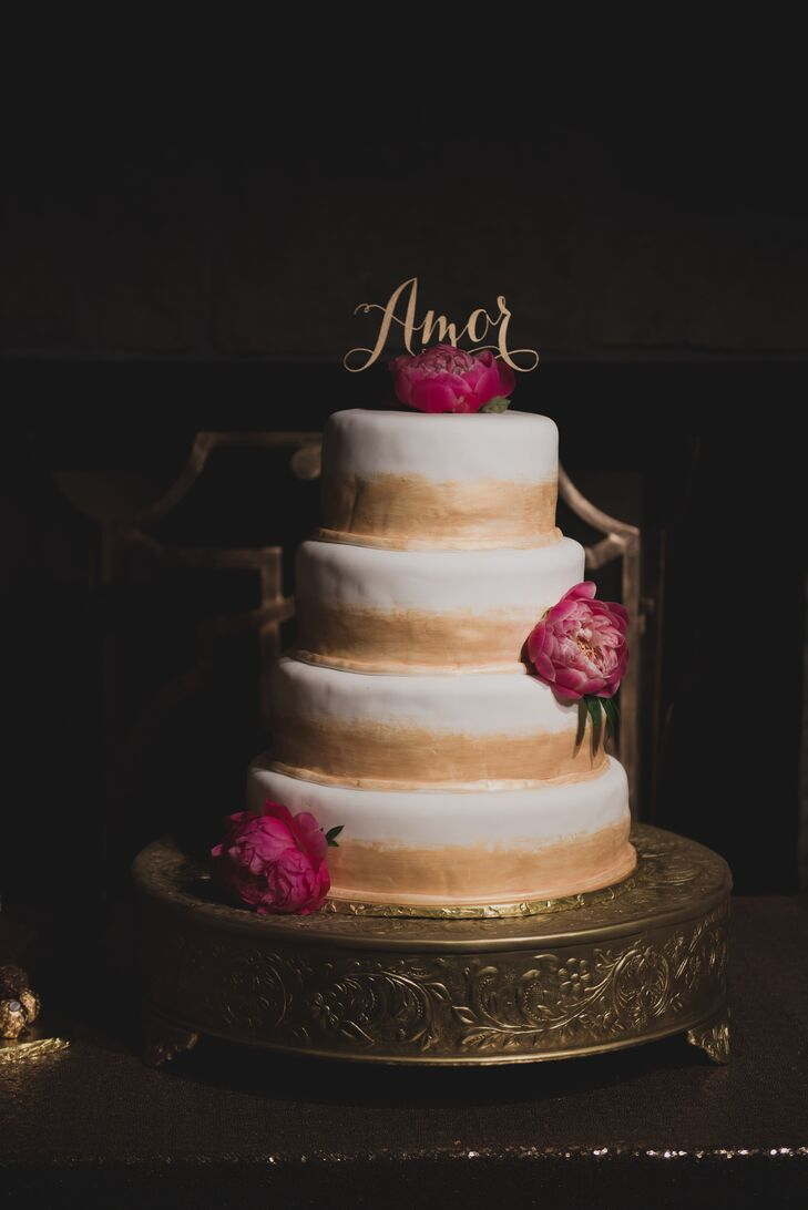 "The couple's wedding cake was half gold, half white icing and was made by Victoria's stepmother. ""My favorite flavor is white cake with raspberry filling, and Evan's was a Ferrero Rocher truffle cake."" The cake was topped with fresh fuchsia florals."