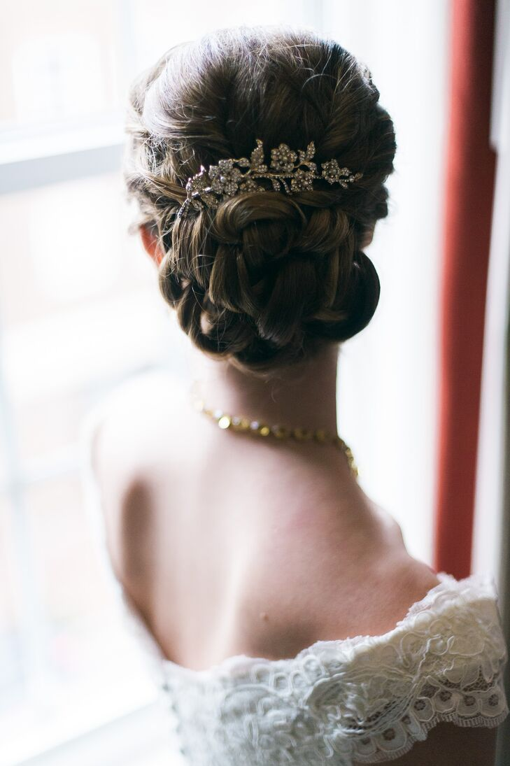 Christine had her hair styled back into a braided bun, done by Alison Harper & Co. She had a gold leaf-shaped clip embellished with crystals pinned to the top of her updo.