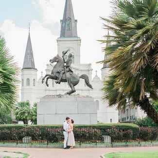 Newlyweds kissing in front of statue in Louisiana