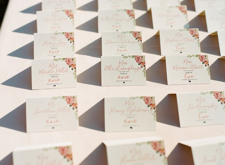 Custom escort cards echoed the design of the invitations with pink flowers and calligraphy.