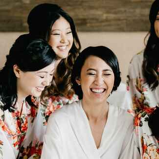 Bride laughing with bridesmaids in robes