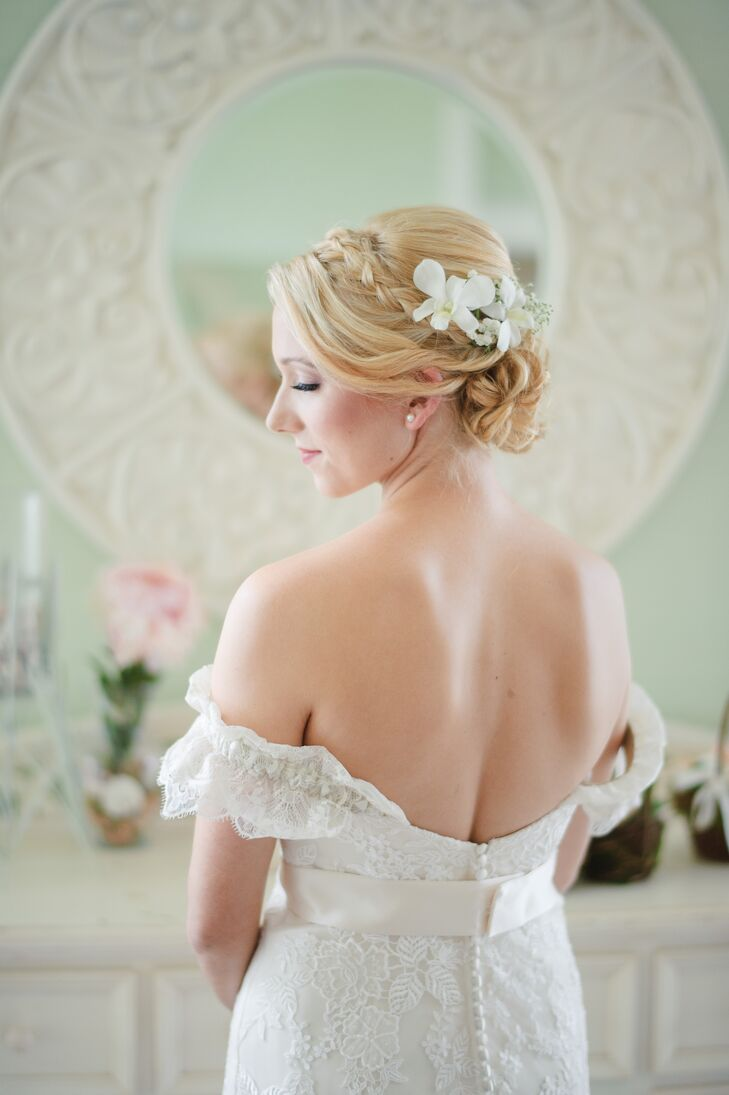 "Erica had her hair styled in a romantic updo with a simple braid. White orchids and baby's breath were placed above the bun in lieu of a traditional veil. ""For jewelry I wore pearl earrings Cole gave me previously and nothing else. I felt too much would take away from the dress,"" she says."