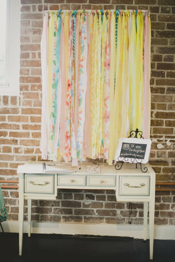 The guest book was displayed on a vintage dresser, with colorful ribbons hanging behind it. A small chalkboard sign provided a hashtag for guests to post pictures on Instagram.