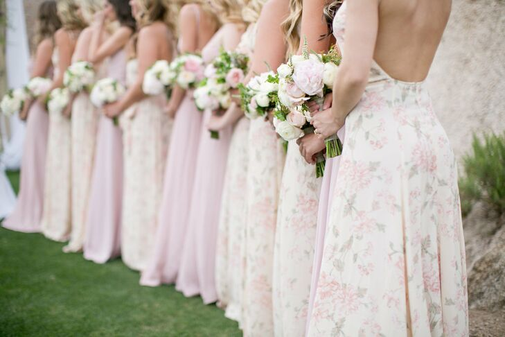 Bridesmaids wore soft and flowing gowns in alternating light pink and floral from Reformation. Their bouquets featured light pink and white florals.