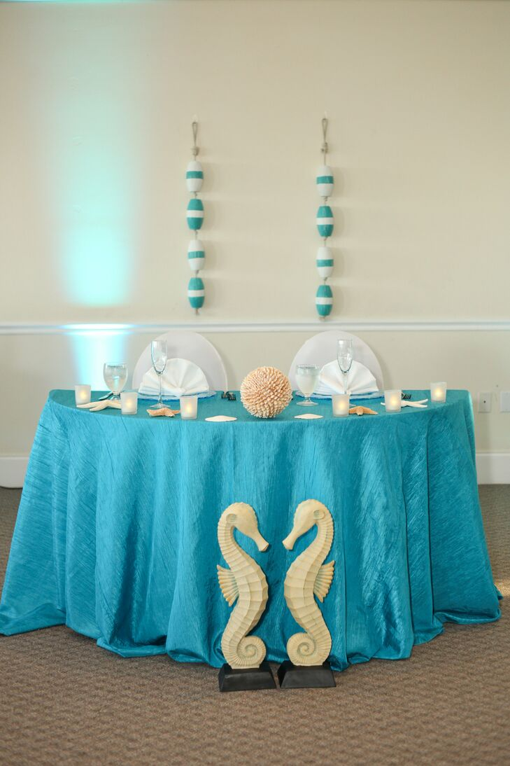 With their ocean and beach theme in mind, two neutral seahorse accents were placed in front of the couple's sweetheart table. Assorted starfish and a large ball that resembled coral covered the blue linens as blue and white buoys accented the wall. They even chose clear blue chargers with a wave pattern to complement the decor.