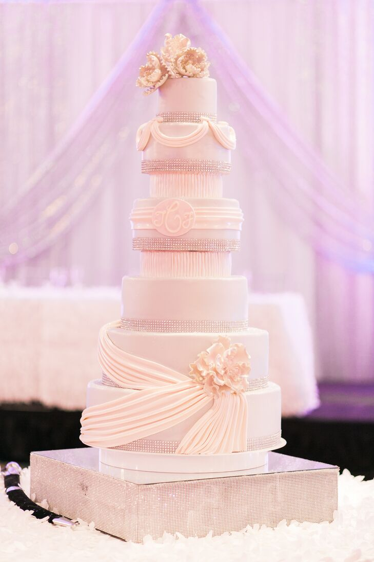 "The couple chose a five-foot tall confection baked by Michael Angelo's Bakery. It was accented with rhinestones, ivory fondant, a custom ""T & F"" monogram and cake flowers."