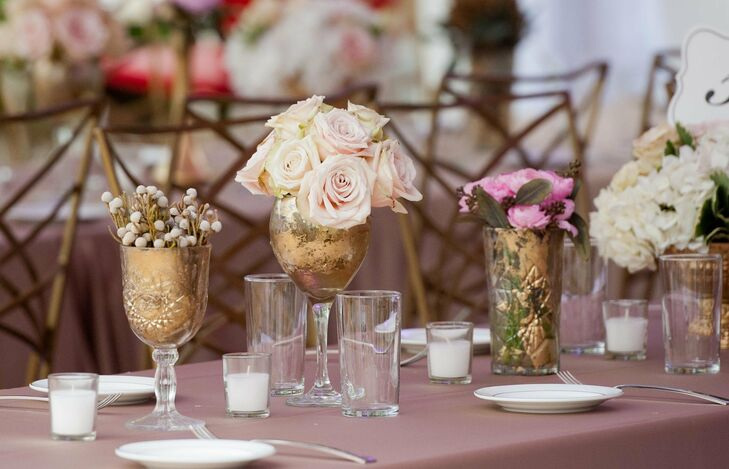Containers of varying shapes and sizes, from small vases to large goblets and wine glasses, were painted a muted gold and filled with blush blooms.