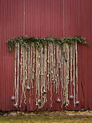 DIY metallic rope and gardland backdrop for an outdoor wedding ceremony