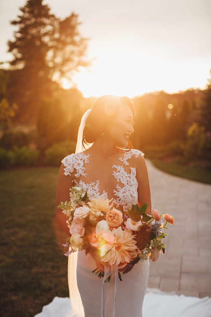 For Yan's walk down the aisle, Sweet Annie Floral Design arranged a lush, still-life-inspired bouquet of full dahlias, garden roses and ranunculus in soft shades of blush, coral and peach. The textured bouquet popped against Yan's illusion lace gown for a dramatically romantic look.