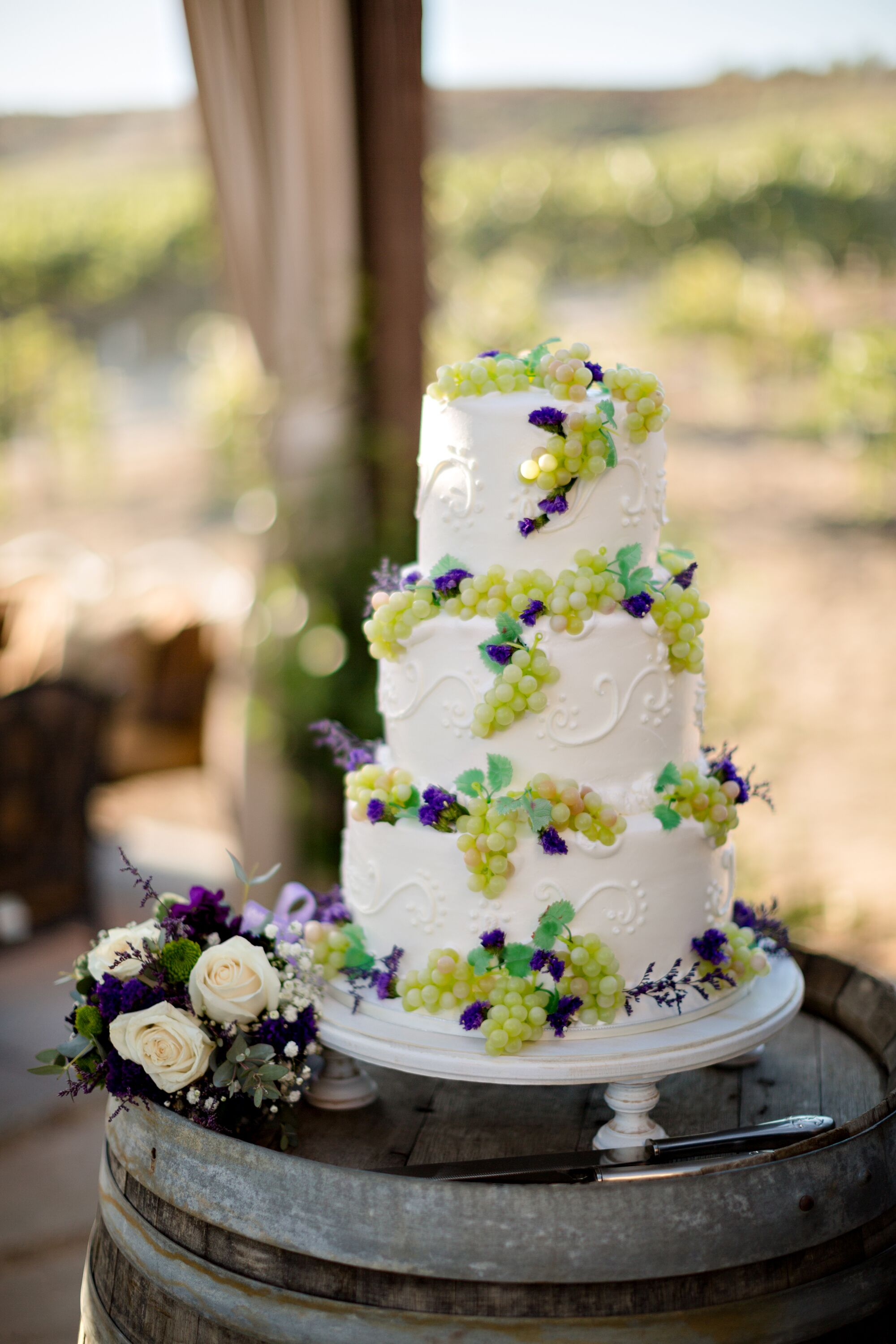 ivory wedding cake accented with grape decor. Black Bedroom Furniture Sets. Home Design Ideas