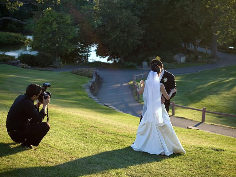 Bride and groom working with photographer