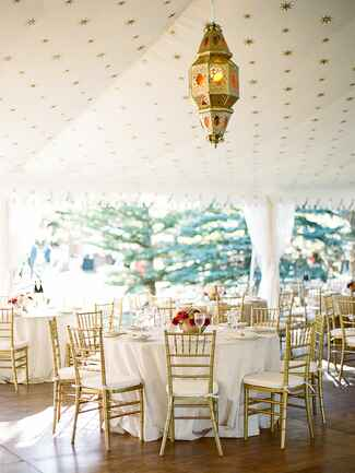 Round reception tables with gold chairs in tent