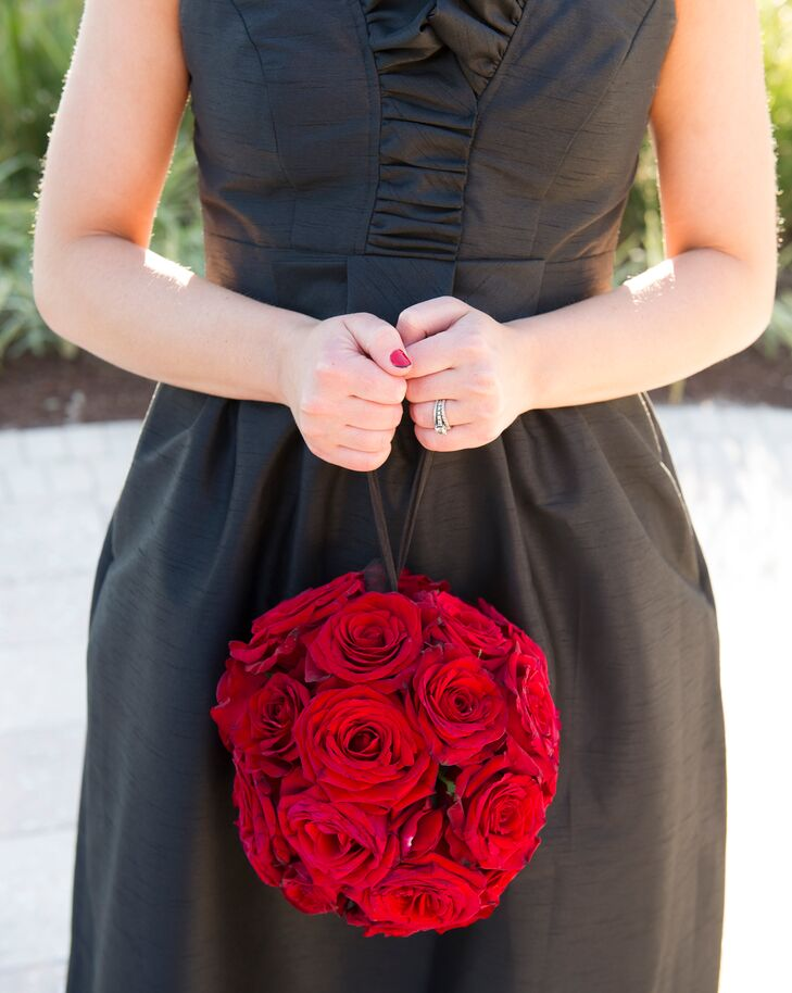 Each of Courtney's bridesmaids paired her black, floor-length Alfred Sung dress with an eye-catching red rose pomander.