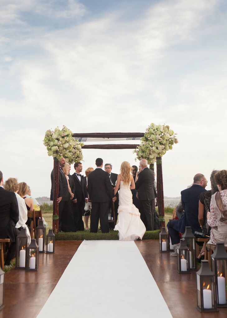 Nora and Michael married under a simple bamboo and tall grass huppah with bunches of hydrangeas, blush spray roses and green vibernum in the corners. The aisle had a white runner and was lined with lamps.