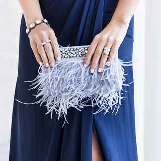 woman holding feathered clutch