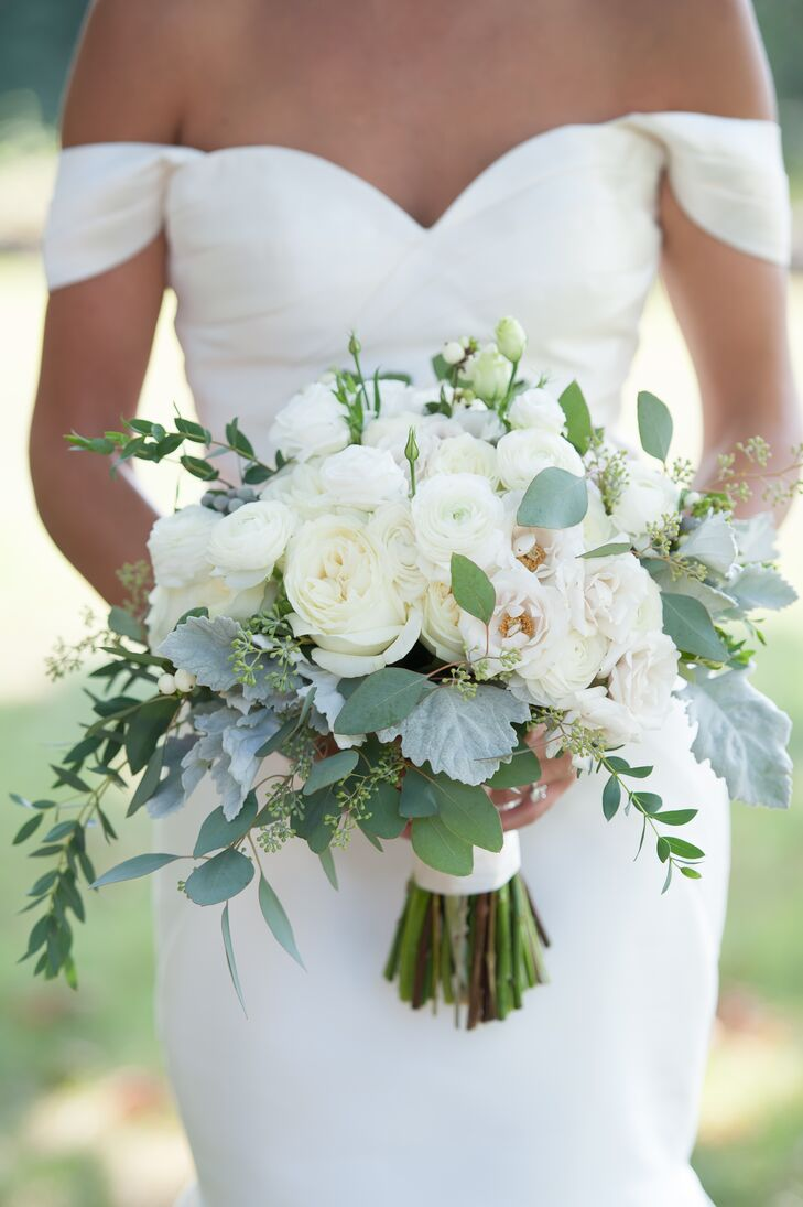 For Rebecca's walk down the aisle, Dragonfly Events created a standout romantic bouquet filled with fresh white blooms and cool textured accents. The hand-tied arrangement featured roses, ranunculus, liasianthus, dusty miller, snowberry, eucalyptus and bay laurel, and was finished with a length of white silk ribbon.