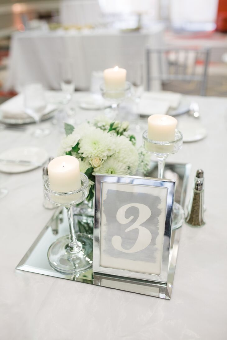 Using a classic color palette of white and metallic/silver the bride and groom decorated the tables with centerpieces that consisted of flowers in vases, candelabras, and tiered stemmed candles.