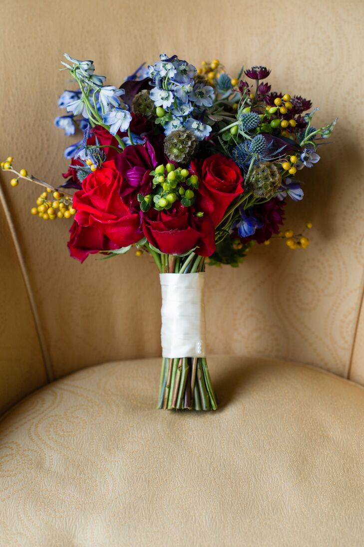 The brides carried autumnal bouquets of red, russet and burgundy roses, burgundy scabiosa and blue and green thistle.
