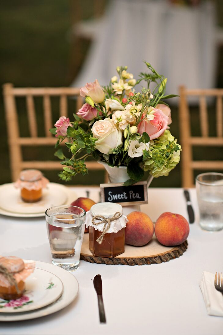 To honor the farm's seasonal delicacies, centerpieces incorporated ripe juicy peaches and homemade jars of honey that doubled as wedding favors. The peach pink rose floral arrangements matched the bouquets, and chalkboard table numbers named some of the couple's favorite places in Pennsylvania.