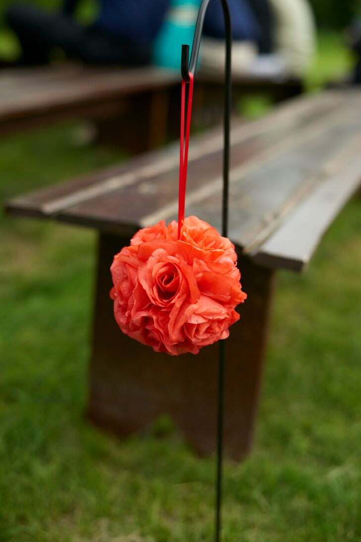 Bright coral rose pomanders lined the aisle for the outdoor farm ceremony at Hope Glen Farm in Cottage Grove, Minnesota.
