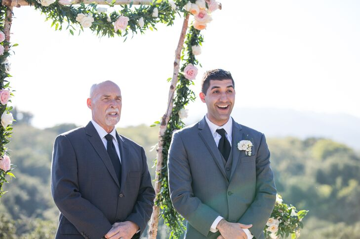 Jeff stood at the altar wearing a single ivory rose boutonniere accented with bouvardia pinned onto his charcoal-gray suit jacket. He wore a black classic tie over his white collar dress shirt, completing his look for the wedding day.