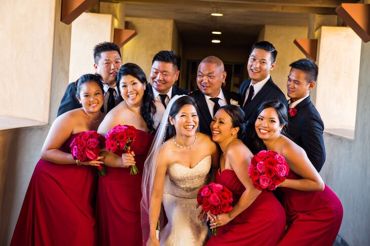 AnhThu and Lan posed with their wedding party, with the groomsmen wearing black suits and ties that matched the groom; the bridesmaids wore strapless, red floor-length dresses. The bridesmaids held round bouquets filled with red roses that matched their outfits.