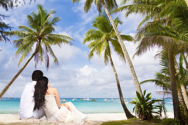 Bride And Groom Sitting On Beach After Destination Wedding