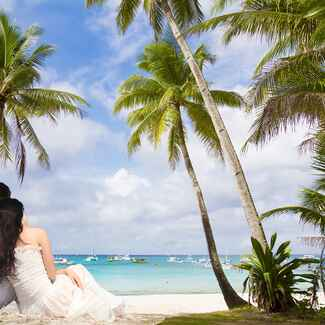 Bride and groom sitting on beach after destination wedding