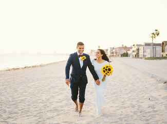 Bride and groom on a beach with a bouquet of sunflowers