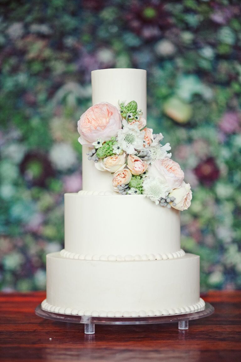 Cream Four Tiered Wedding Cake With Blush And Green Flower Arrangement