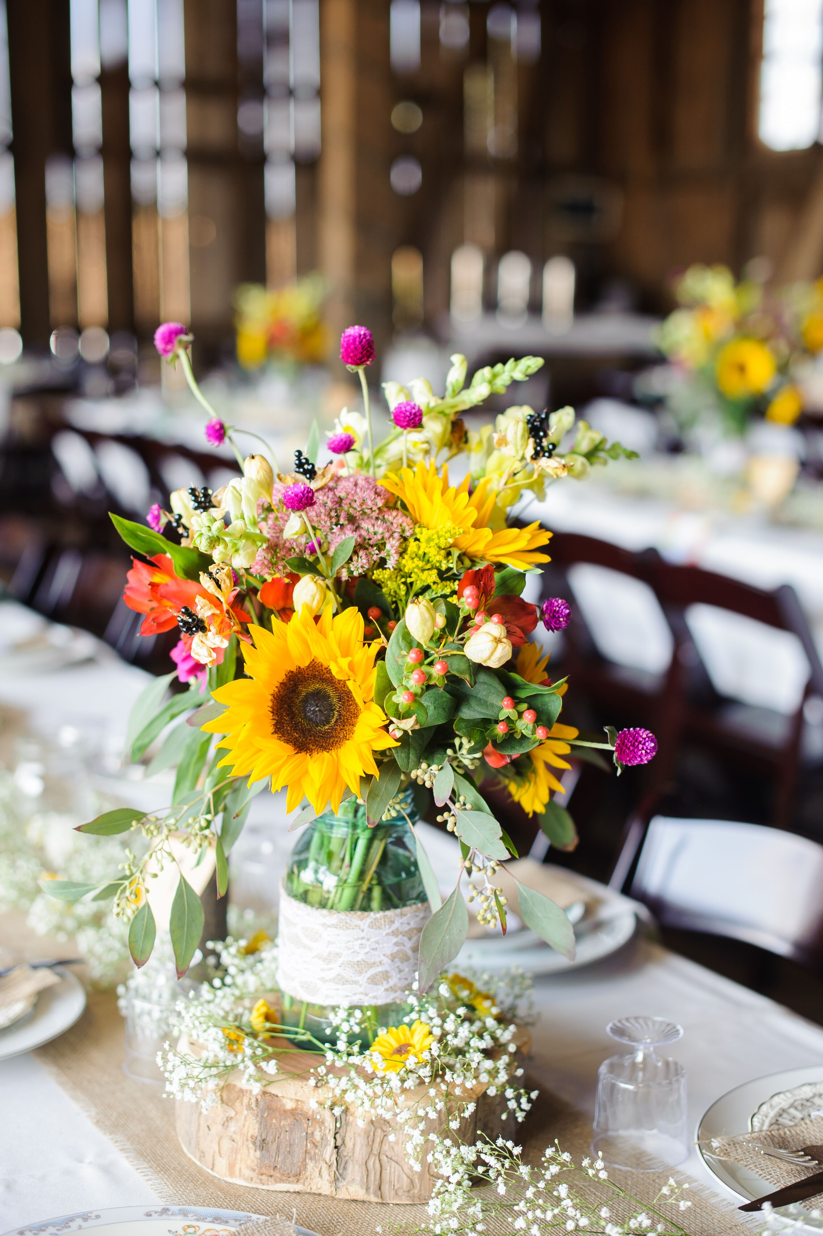 Pink And Yellow Centerpieces In Mason Jars On Burlap Table
