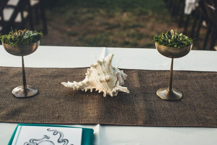 A large conch shell surrounded by gold vases with succulents decorated the dining tables dressed in burlap runners.
