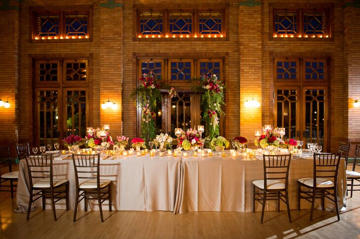 With brick walls and detailed windows as the backdrop, the romantic head table was decorated with chiavari chairs, greenery, flowers and candles.