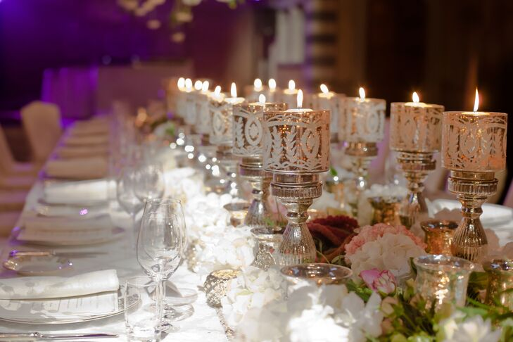 The long dining table at the reception was lined with two rows on mercury-glass candleholders. These centerpieces were wreathed by pink and white flowers.