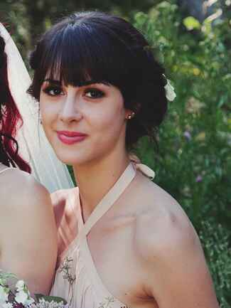 Boho bridesmaid hairstyle with loose updo and bangs