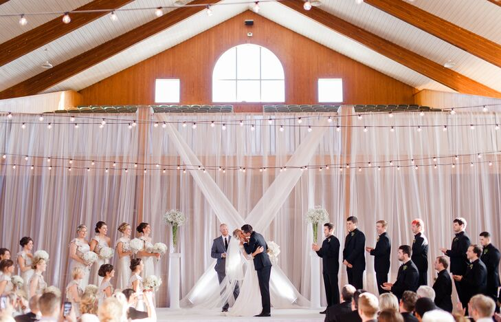 Jenna and Tyler shared their first kiss in front of the backdrop draped with white linens, under strings of twinkling lightbulbs. Two pillars holding up tall baby's breath arrangements stood on each side of them.