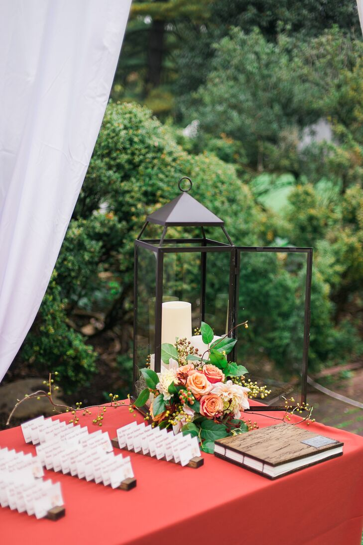 The table displaying the guest book and escort cards had a tall black lantern decorating the corner, with its open door that had a flower arrangement filled with orange blooms spilling out.