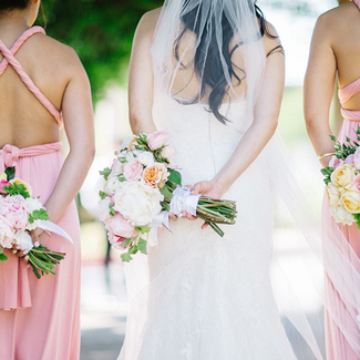 Bride with bridesmaids and bouquets back turned