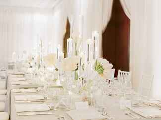 All-white wedding reception with tulips and candles