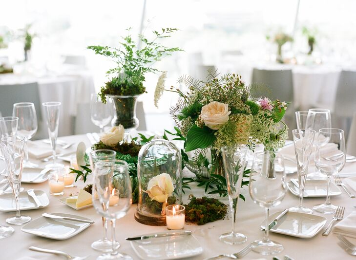 The reception tables at Walker Art Center were topped with a variety of high and low centerpieces and glass details. Ferns, green trick dianthus, roses, wildflowers and moss brought the outside in for a rustic aura.
