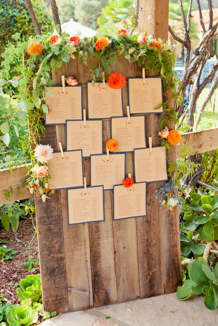 Guests were listed in alphabetical order on square pieces of light brown paper bordered with navy blue, with table numbers next to their names. The seating assignments were attached to wire by clothespins and displayed on a wooden board, accented with colorful flowers and greenery on top.