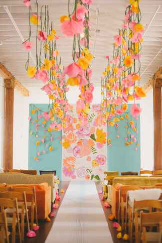 Hanging vibrant paper flowers at indoor ceremony site.