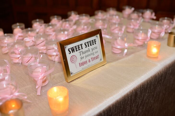 Small mason jars filled with pink macarons were given to guests as favors.