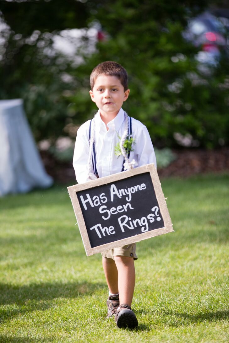 "The couple sent their ring bearer down the aisle with a rustic chalkboard sign bearing a cheeky message, ""Has anyone seen the rings?"""
