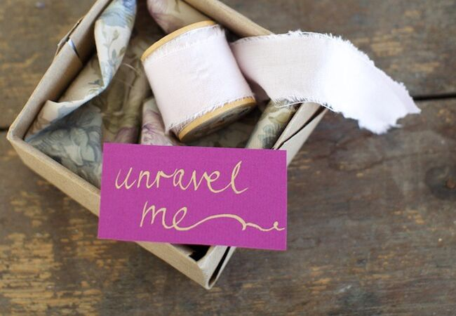 "fabric on spool and card that says ""unravel me"""