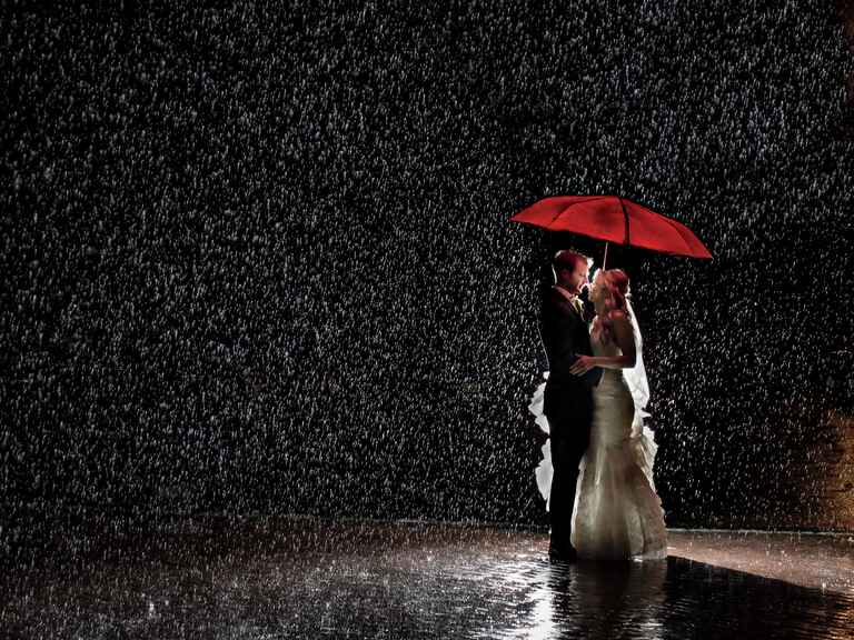 Dramatic wedding photograph of bride and groom under umbrella