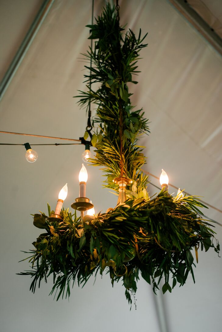 Instead of having a strictly floral chandelier made by Belovely Floral and Event Design, Gina and Mike had Woolverton Inn's lighting wrapped in garlands. Eucalyptus, fern leaves and other added greenery decorated each one between vintage-inspired electric candlesticks.