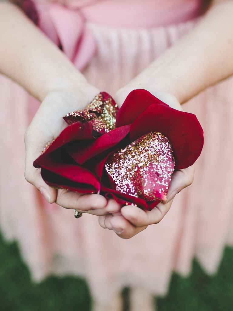 Bridesmaid holding glitter-covered red rose petals