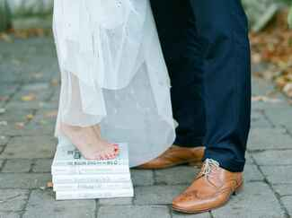 Barefoot bride standing on a stack of books with groom