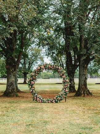 Giant floral circle installation for an outdoor wedding ceremony altar